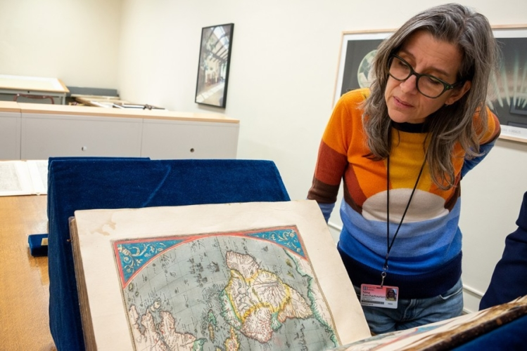 Artist Nina Katchadourian examining maps in The Huntington's library collections, 2019.