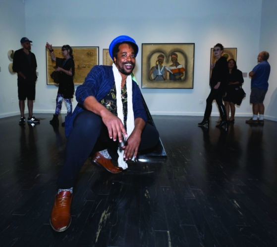 "Umar Rashid at the opening of ""Umar Rashid (Frohawk Two Feathers): The World You Know Is A Fiction. You Know We Had To Do A Remix, Right? Vignettes of The Frenglish Empire in North America (1780-1795),"" Vincent Price Art Museum, East Los Angeles College, 2019."